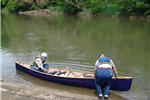 A group of men lowering a canoe into the water